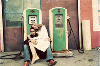 wedding engagement photo of couple sitting on green retro antique gas pumps