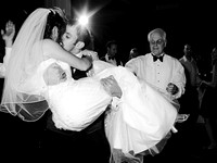 black and white photo of jewish groom holding jewish bride while kissing at their wedding reception
