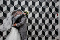 bride and groom kissing under veil against black and white mural at mississauga city hall