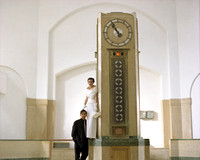 bride and groom standing beside clock at the art deco R C Harris water treatment plant in toronto canada