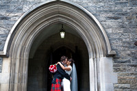interracial wedding couple kissing in the doorway at the university of toronto