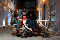 engagement couple sitting on skids warehouse in toronto at night